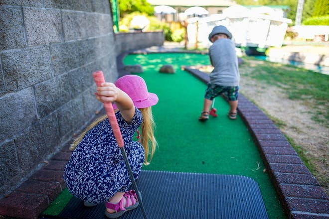 Young boy and girl playing crazy golf