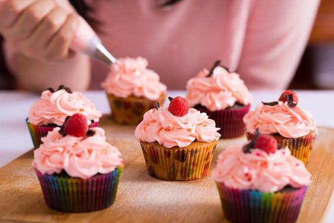 teenage girl decorating cupcakes with pink icing and raspberries