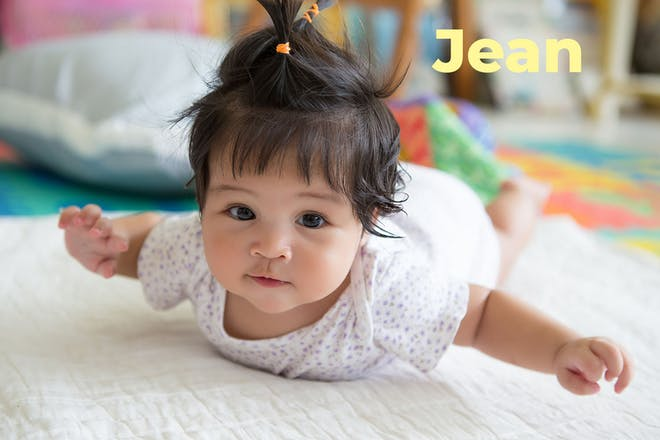 Baby lying on front lifting arms. Name Jean written in text