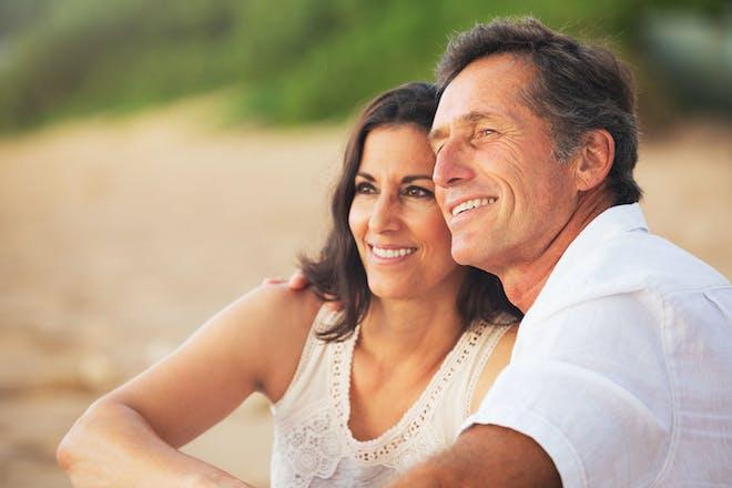50多岁的情侣坐在沙滩上