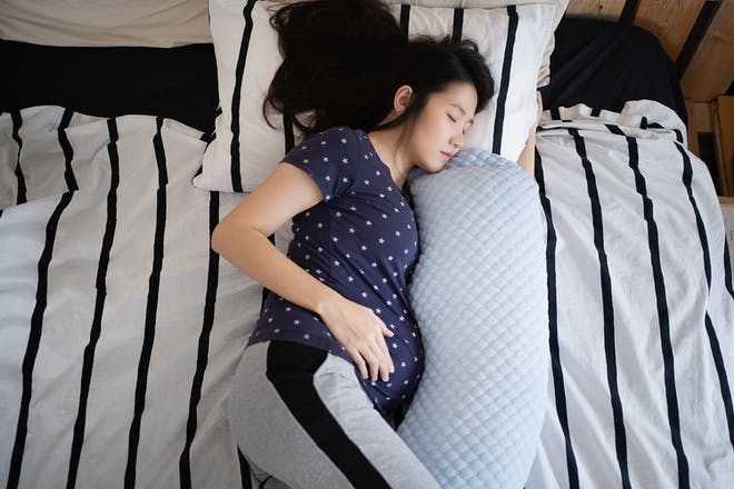 Pregnant woman sleeping with pregnancy pillow