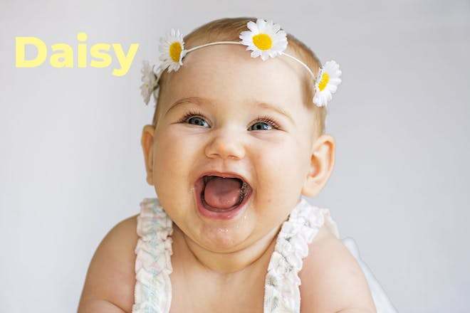 Baby wearing daisy chain on head. Name Daisy written in text