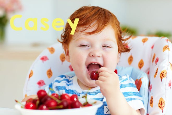Baby with red hair sitting in high chair eating cherries. Text says Casey