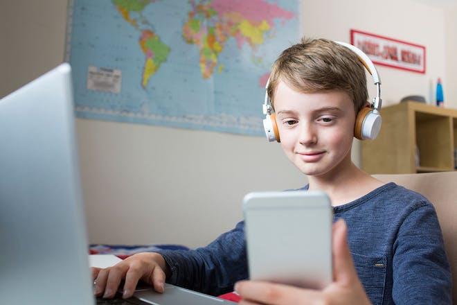 Teenage boy using laptop and phone and wearing headphones in his bedroom