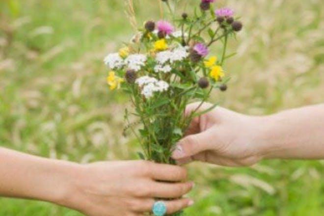 hands holding flowers in field