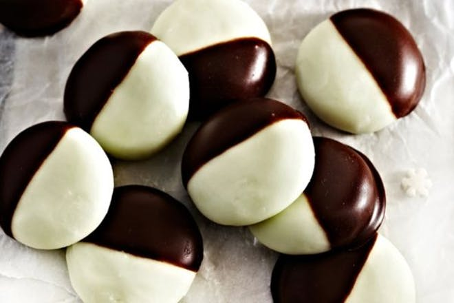 Peppermint creams half dipped in chocolate on a plate