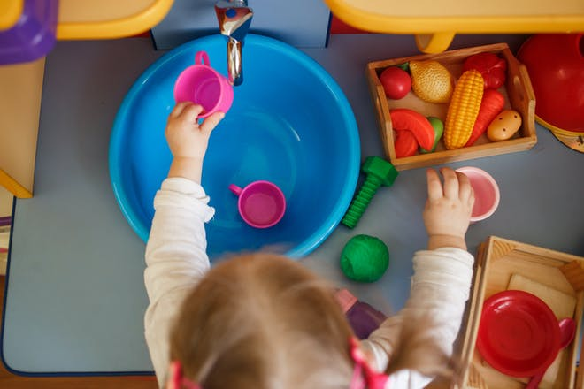child with plastic bowl of water and toys