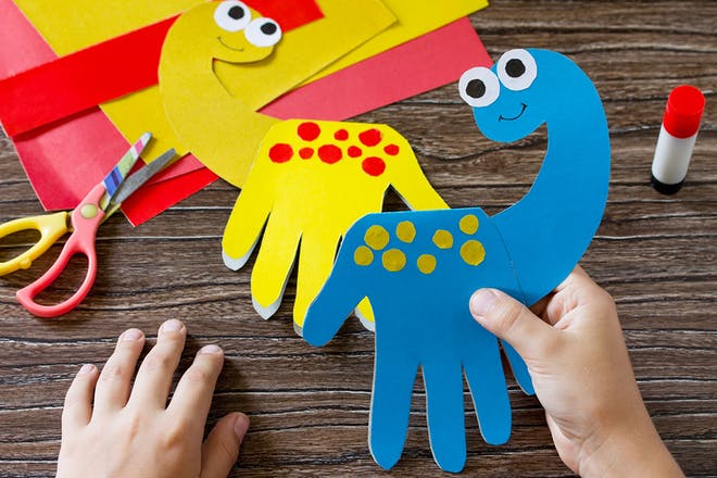 Hand prints cut out of coloured card with head attached so look like diplodocus dinosaur