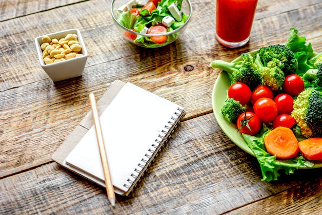 A notebook alongside a plate of healthy vegetables