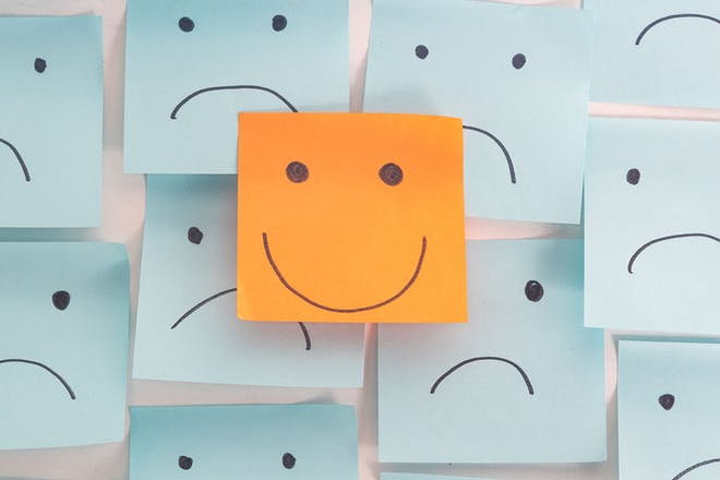 Post it notes with smiling and unhappy faces drawn on