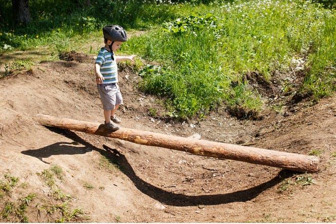 boy walking along log
