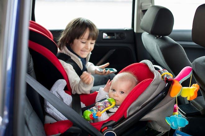 young child in forward-facing car seat and baby in backward-facing car seat