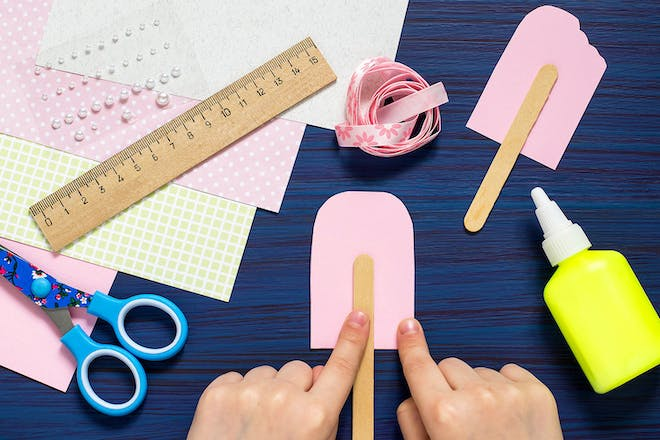 Child making ice lolly shape from card