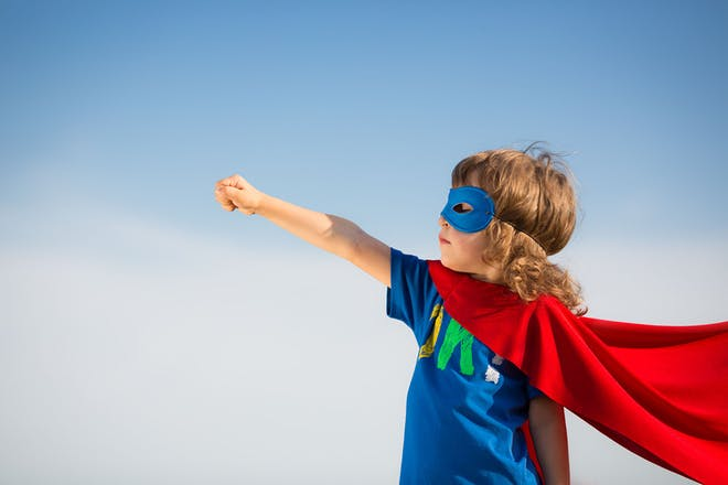 Young boy with superhero's cape and mask
