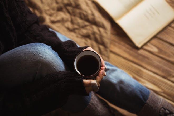 woman holding mug of tea reading a book