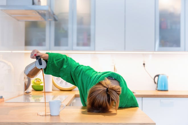 tired woman with head on counter