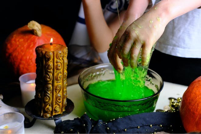 Kid playing with green slime in party bowl next to candle and Halloween pumpkin