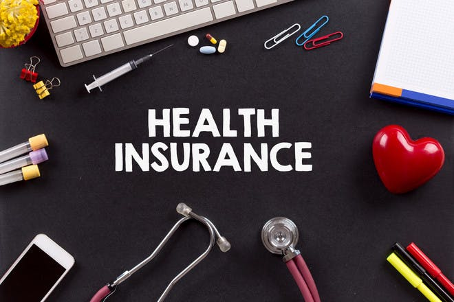 letters spelling out 'health insurance' on a black background next to a keyboard and medical supplies