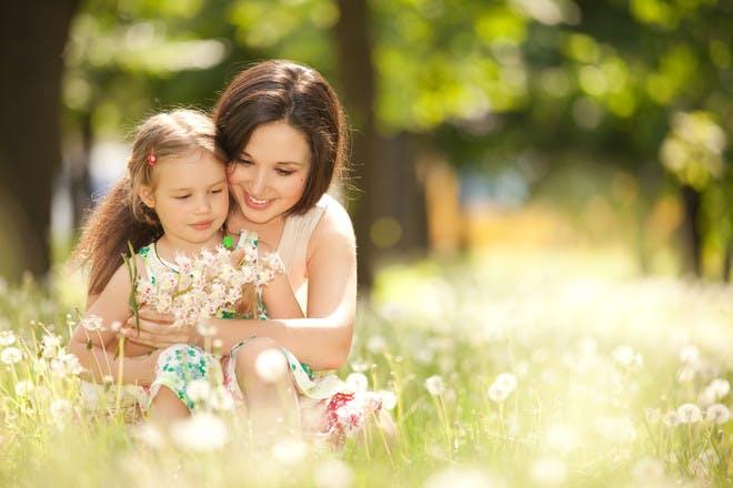 Mum hugging daughter in field