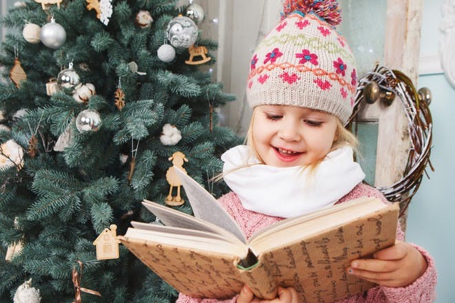 girl in beanie reading book