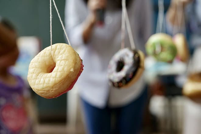 Iced doughnuts hanging on a string for a Halloween party game