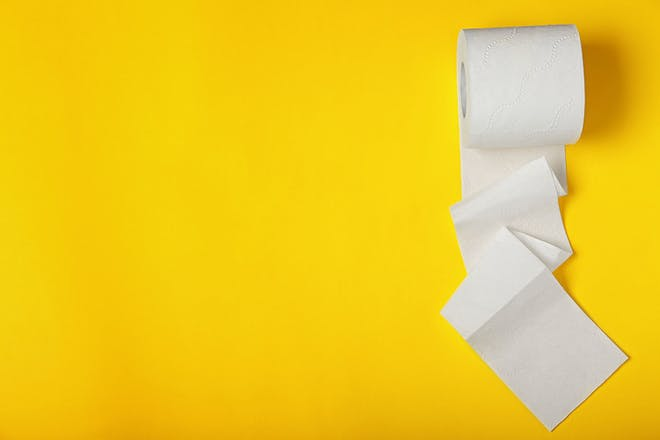 roll of toilet paper on yellow background