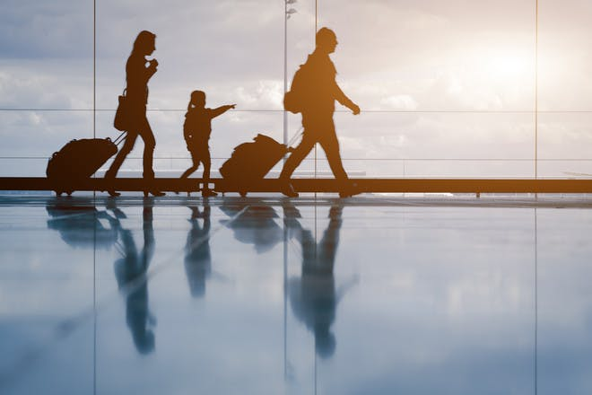 Family with luggage walking through an airport