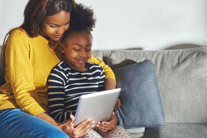 Girl sits on mother's knee playing with iPad