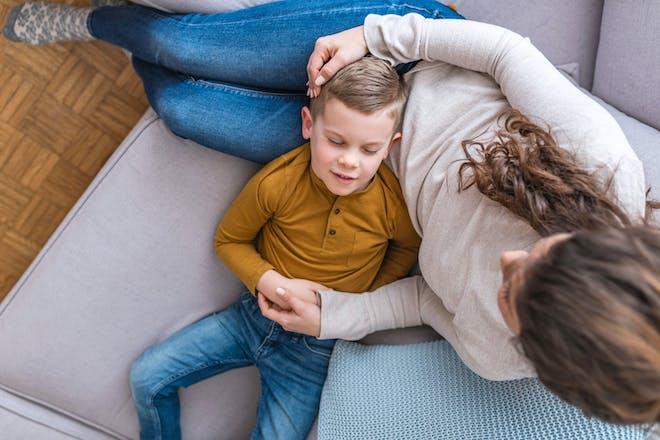 Boy lying on mum's lap on sofa