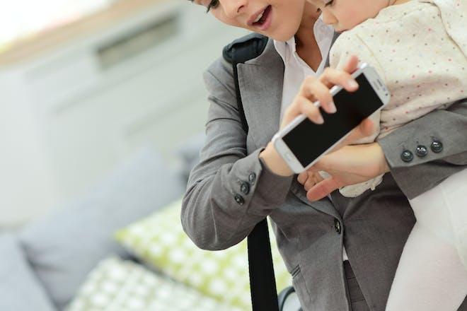 Mum holding baby checks phone