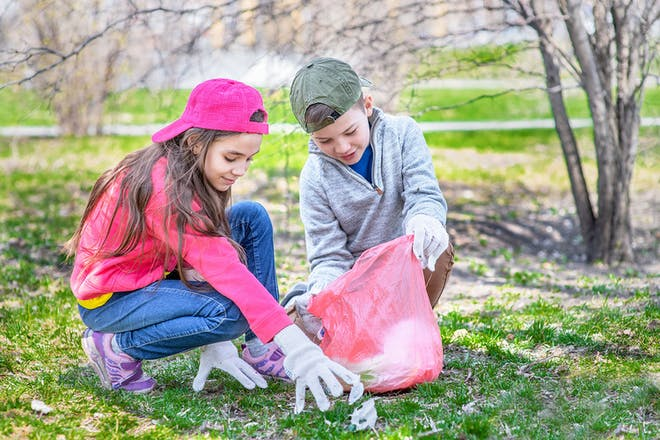 boy and girl collecting litter in the park