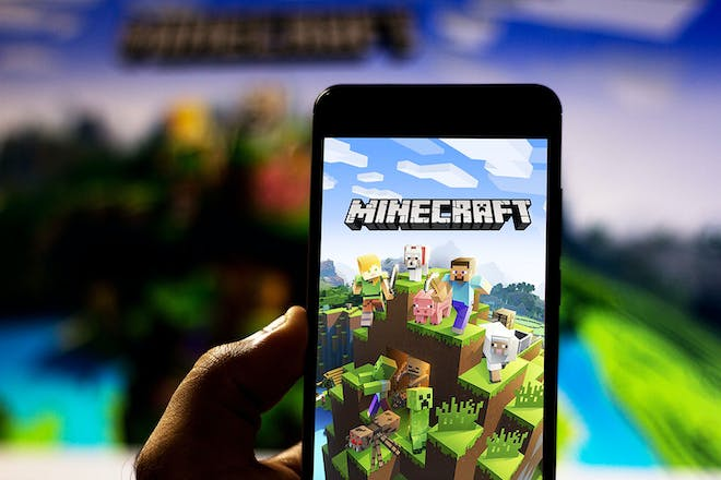 Child holding phone with the Minecraft app downloaded