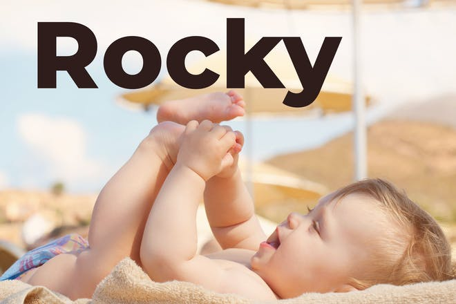 Baby on the beach with Rocky written in text