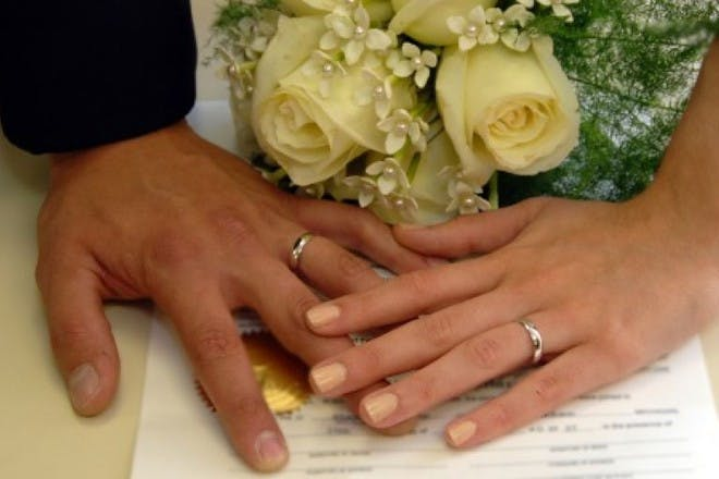 man and woman's hands with rings on and rose in the background