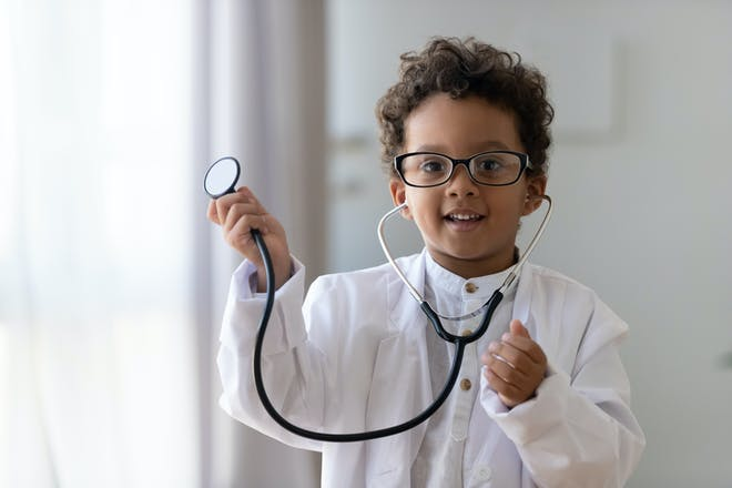 Toddler dressed in doctor costume with a stethoscope for Halloween party