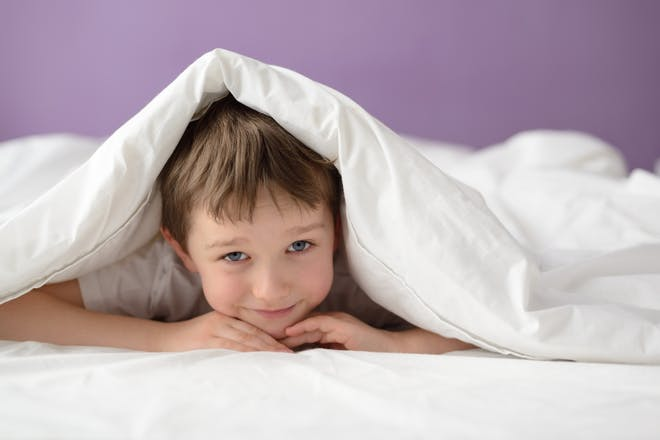 smiling child hiding under duvet