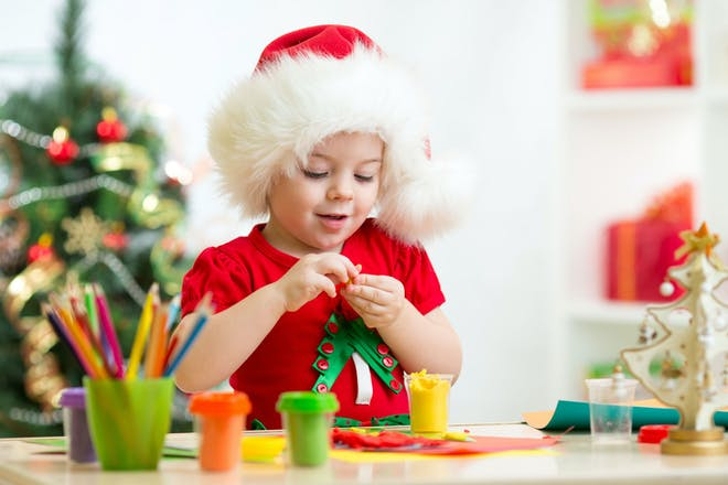 A child wearing a Santa hat making Christmas tree decorations