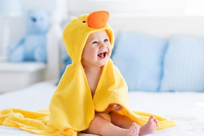 Happy laughing baby wearing yellow hooded duck towel sitting on parents bed after bath or shower.