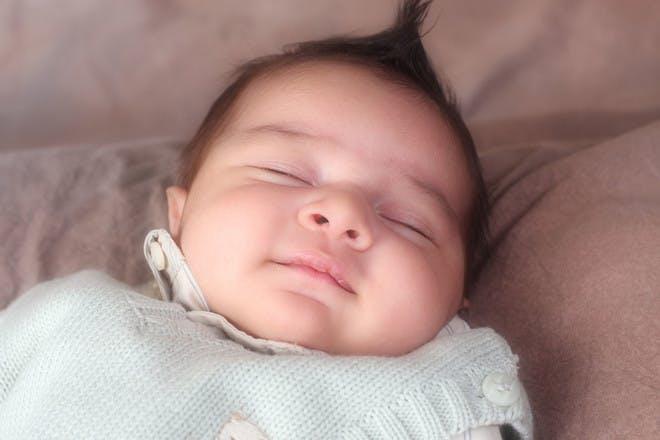 Sleeping baby in a blue jumper