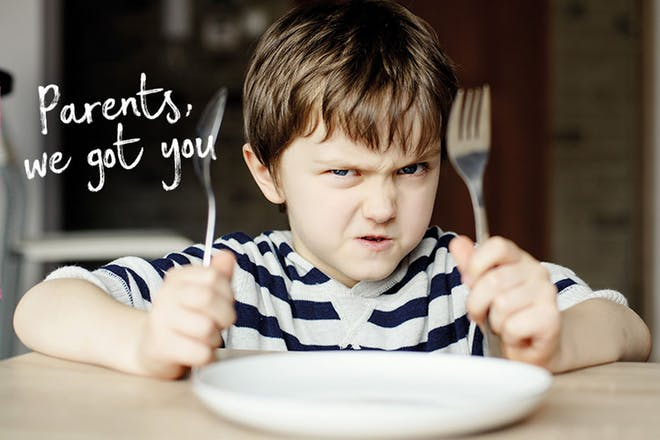 Boy holding knife and fork up next to empty plate