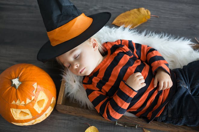 Toddler sleeps on floor next to Halloween pumpkin and wearing witch's hat