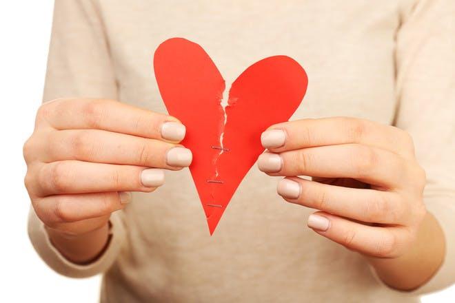 hands tearing paper heart