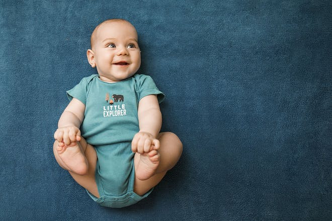 baby holding feet in blue babygro