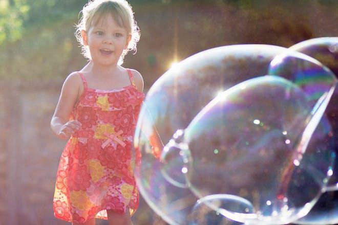 girl running towards giant bubble