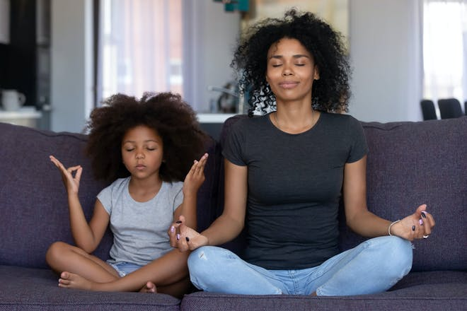 Mum and daughter doing breathing exercises cross-legged on sofa