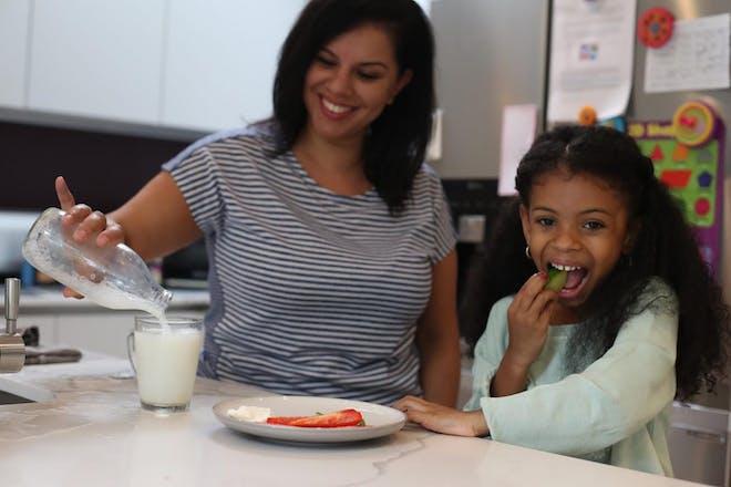 Mum and daughter eating at counter