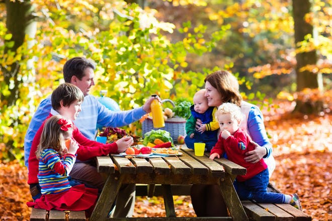 happy family siting at picnic table