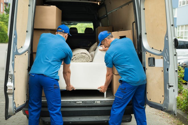 House removers putting sofa in van