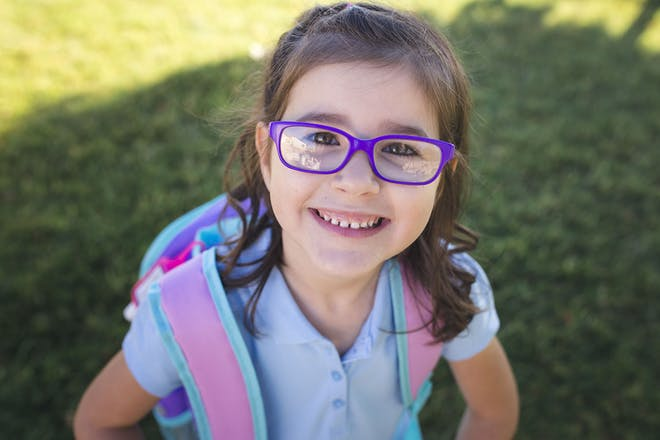Little girl wearing school polo shirt and back pack