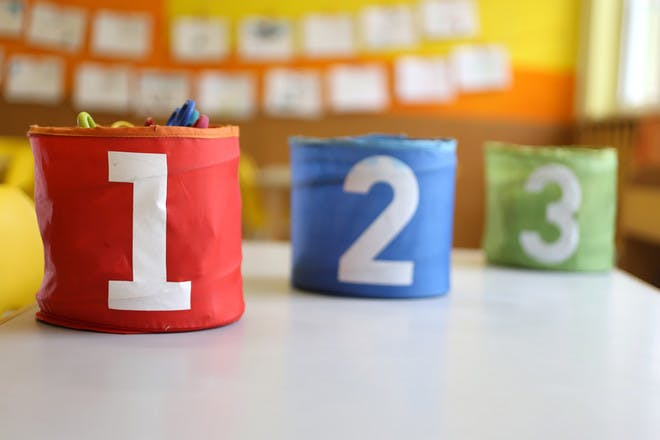 colourful storage pots with numbers on them in classroom